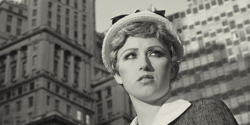 Eine Frau steht in New York vor großen Bürogebäuden in einer weißen Bluse und einem grauen Mantel mit einem weißen Hut auf dem Kopf und schaut an der Kamera vorbei.