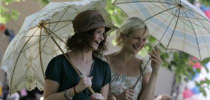 Zwei kostümierte, fröhliche Frauen mit Schirmen