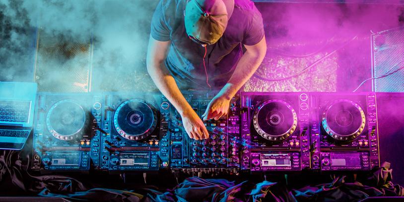 Ein Dj bedient sein DJ Pult, die Umgebung ist nebelig