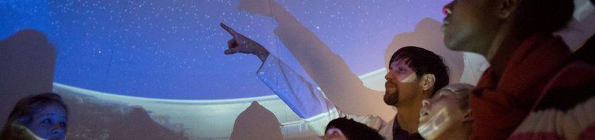 Ein Mann zeigt Kindern das Bild des Sternhimmels