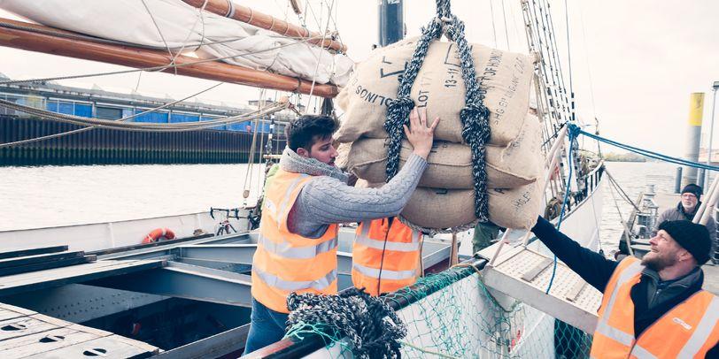 Zwei Männer stehen auf einem Segelschiff und reichen einem anderen Mann drei Säcke Kaffee