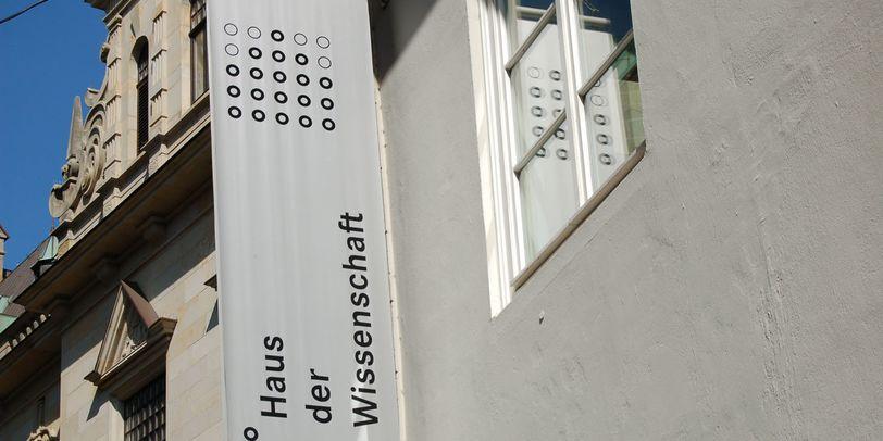 """Eine Fahne mit der Aufschrift """"Haus der Wissenschaft"""" hängt an der Außenfassade."""