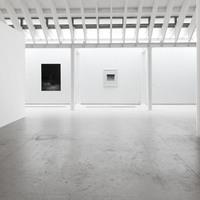 Ein Einblick in die Galerieräume, strahlend weiße Wände mit schwarz-weißen Bildern.