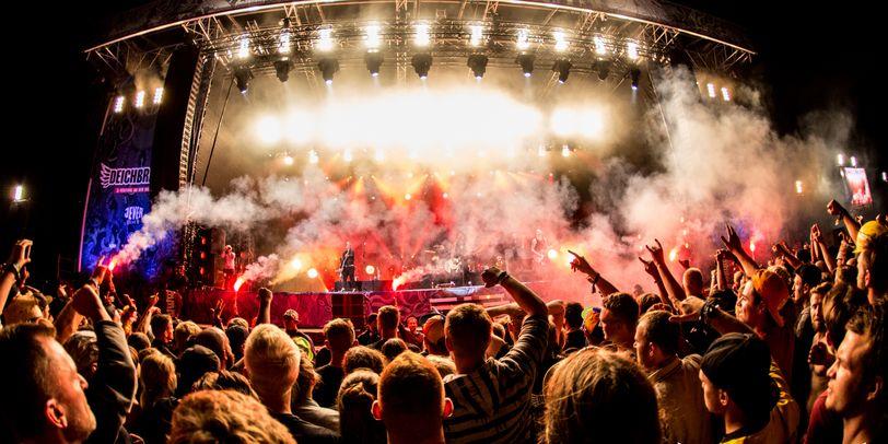 Die Hauptbühne auf dem Deichbrand Festival am späten Abend. Die Broilers singen auf der Bühne und eine große Publikumsmenge feiert davor.