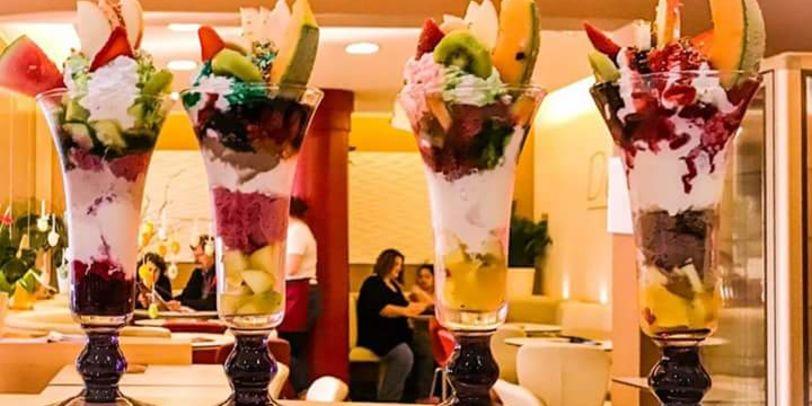 Vier bunte Eisbecher mit Früchten und Dekoration stehen auf dem Tresen.