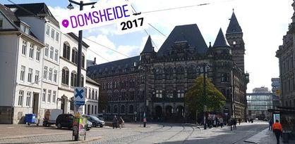 """Zu sehen ist ein kleiner Platz, am Ende des Platzes steht ein großes Gebäude mit mehreren kleinen Türmen. Links im Bild ist eine angeschnittene Häuserreihe zu sehen. Ein lilafarbener Schriftzug mit der Aufschrift """"Domsheide"""" sowie die schwarze Zahl """"2017"""" sind auf das farbige Bild gelegt. Personen laufen über den Platz."""