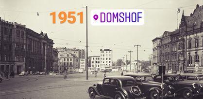 """Im rechten unteren Bildrand steht eine Reihe von Autos geparkt. In der Mitte des Bildes erstreckt sich eine Art Platz mit Straßenbahnschienen. Links, rechts sowie gegenüber des Platzes stehen Gebäude mit zahlreichen Fenstern. Das Bild ist schwarz-weiß. Außerdem sind bunte Schriftzüge auf dem Bild zu sehen: """"1951. Domshof. Staatsarchiv Bremen""""."""
