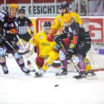Zwei verschiedene Eishockey Teams duellieren sich vor dem Tor.