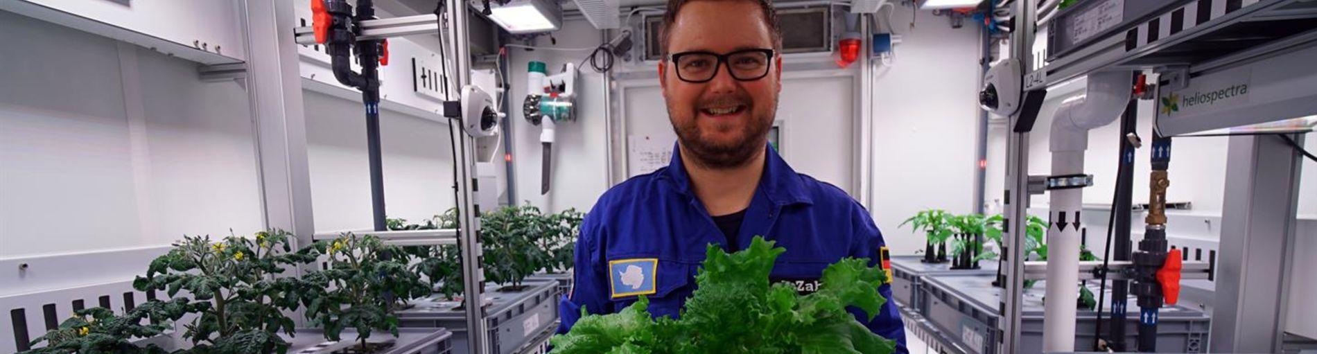 Ein Mann, der Salat in der Hand hält und in einem Labor steht.