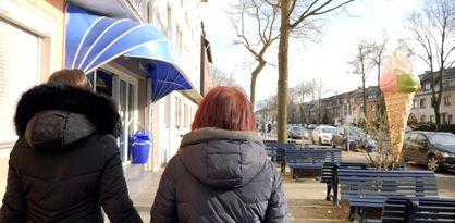 Zu sehen sind zwei weibliche Personen von hinten, die beide eine Winterjacke tragen und an einer Straße entlanggehen. Rechts stehen blaue Bänke und eine große Eiswaffel-Figur. Links ist eine blaue Markise zu sehen.