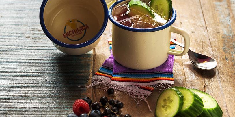 Ein Cocktail namens Enchilada Mule, serviert im Becher. Davor Früchte und Gurken.