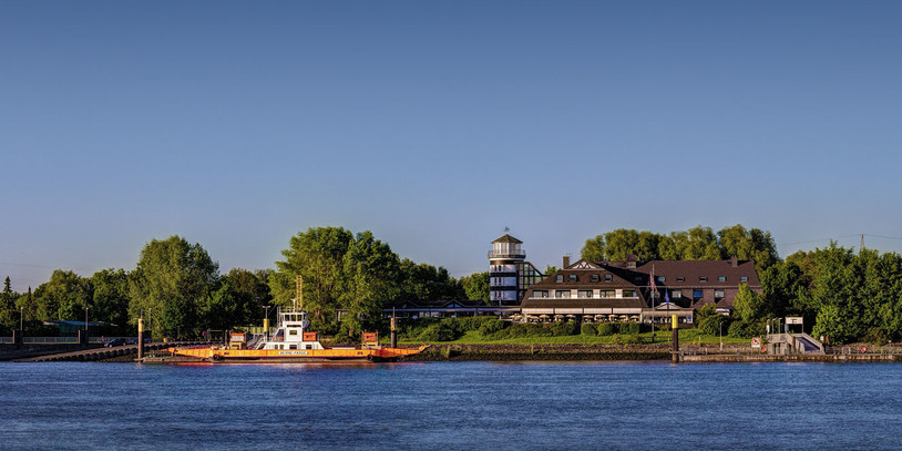 Ein Blick von der anderen Weserseite auf das Ringhotel Fährhaus Farge. Links befindet sich auch ein Schiff.