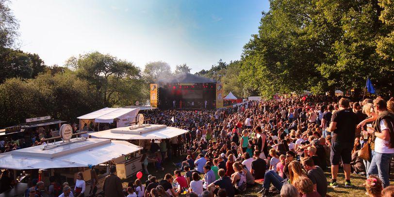 Eine große Bühne auf dem Fährmannsfest. Davor verschiedene kleine Buden und eine große Menge Menschen.