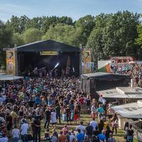 Bühne und Getränkebuden umringt von zahlreichen Festivalbesuchern. Im Hintergrund sind Bäume und ein blauer Himmel zu sehen.
