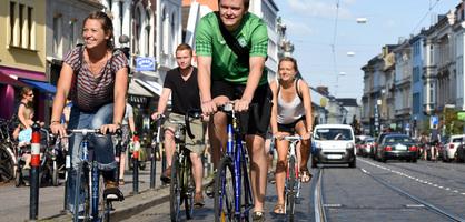 Vier junge Menschen fahren auf Fahrrädern durch eine belebte Straße; Quelle: WFB/Ingo Wagner