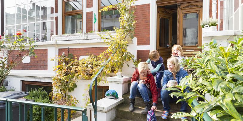 Zwei Frauen und zwei Kinder sitzen auf einer Treppe in einem Hauseingang; Quelle: WFB/Thomas Hellmann