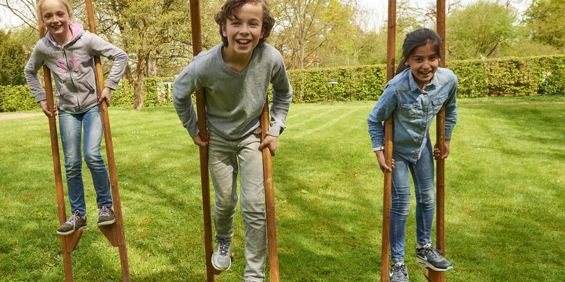 Zu sehen sind drei Kinder, die mit hölzernen Stelzen auf einer grünen Rasenfläche laufen.