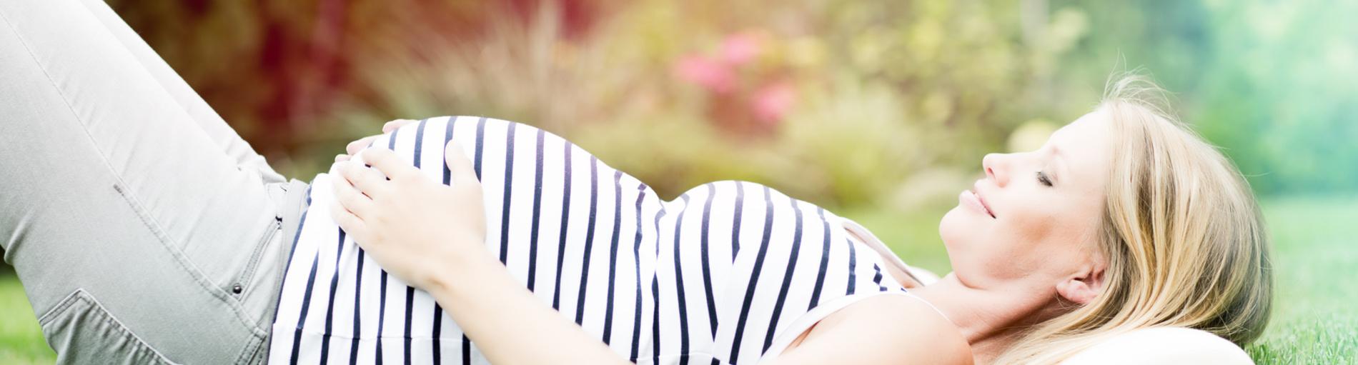 Eine schwangere Frau liegt lächelnd auf einer Wiese (Quelle: fotolia / drubig-photo)