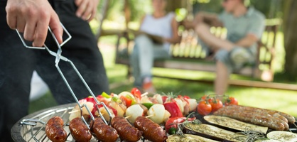 Im Vordergrund ein Grill mit unterschiedlichem Grillgut, im Hintergrund zwei Menschen auf einer Bank. Quelle: fotolia / Photographee.eu