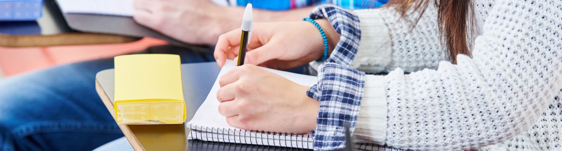 Eine junge Frau schreibt etwas auf einen Block