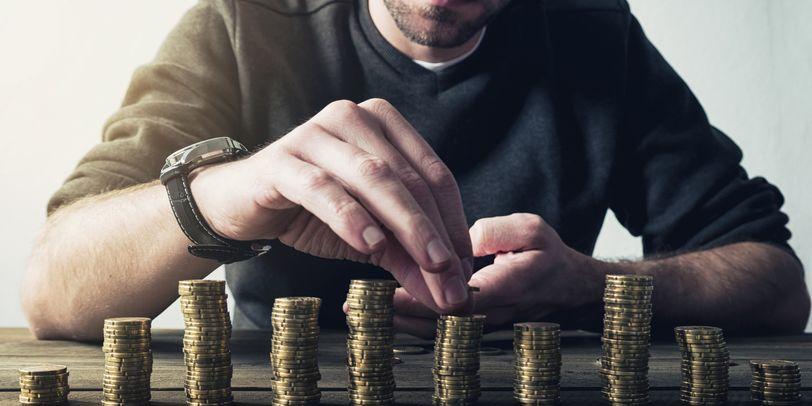 Ein Mann stapelt Geld