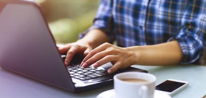 Eine Frau tippt auf einer Laptoptastatur, daneben Kaffeetasse und Smartphone.