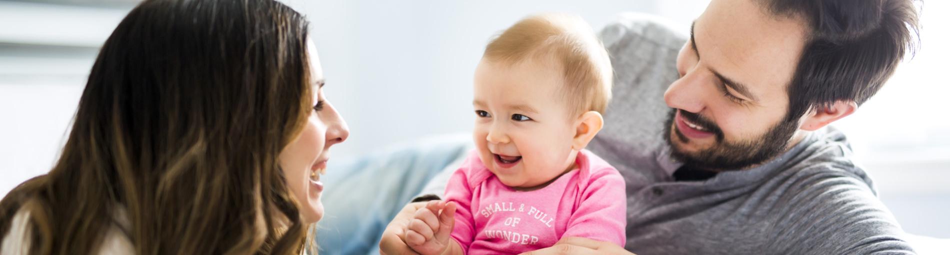 Ein junges Elternpaar liegt mit einem lachenden Kind auf einer weißen Decke.