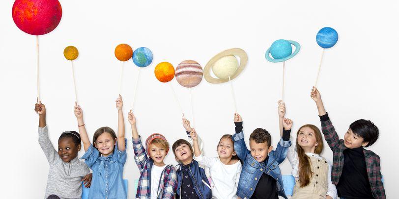 Kinder halten Planeten an Stäben.