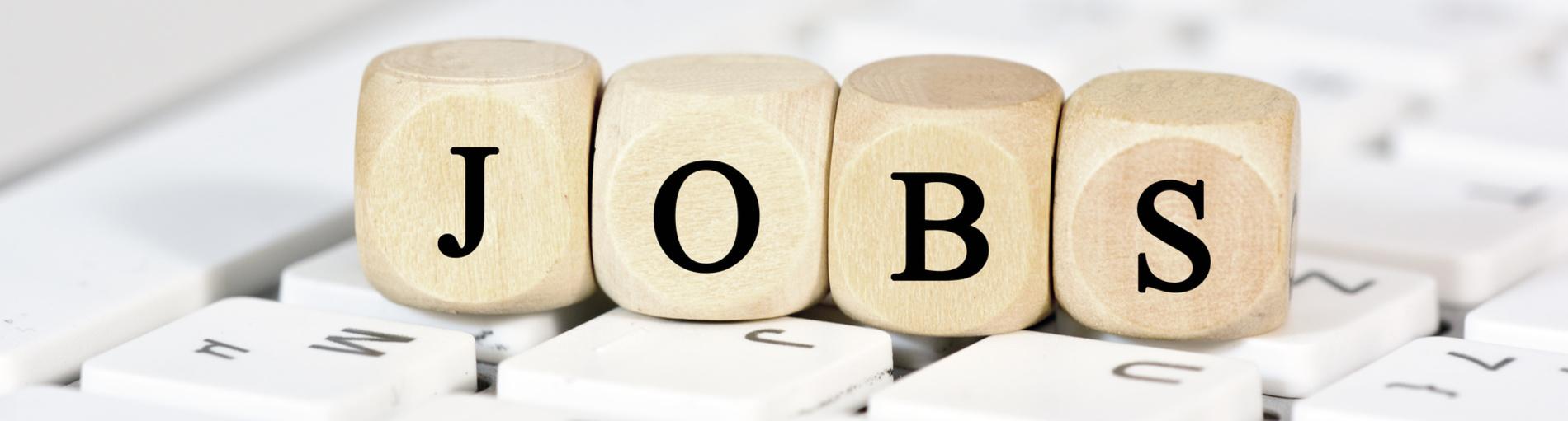 """Vier Würfel mit den Buchstaben """"JOBS"""" liegen auf einer Computertastatur (Quelle: fotolia / Marco2811)"""