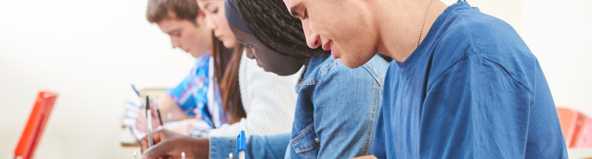 Schüler sitzen in einer Reihe an Tischen und schreiben etwas auf.