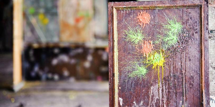 Indoor Paintball-Spielfeld mit sichtbaren Farbspuren auf Holzwänden.