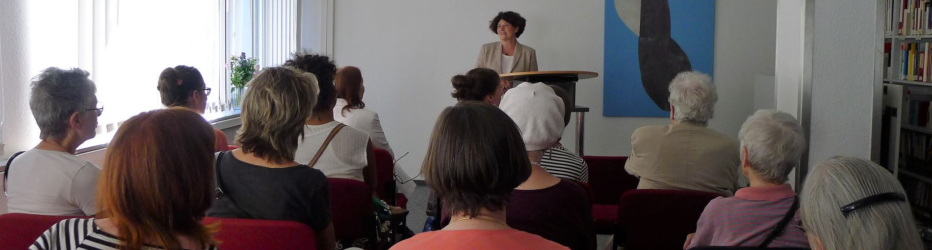 In einem Raum lauschen Frauen einem Vortrag zu frauenspezifischen Themen.