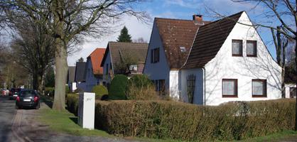 Eine Reihe mit vielen freistehenden Häusern an einer Straße.