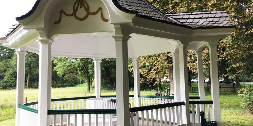 Ein Pavillon aus weißem Holz und mit dunklem Dach. Im Hintergrund sind Bäume und eine Wiese zu erkennen.