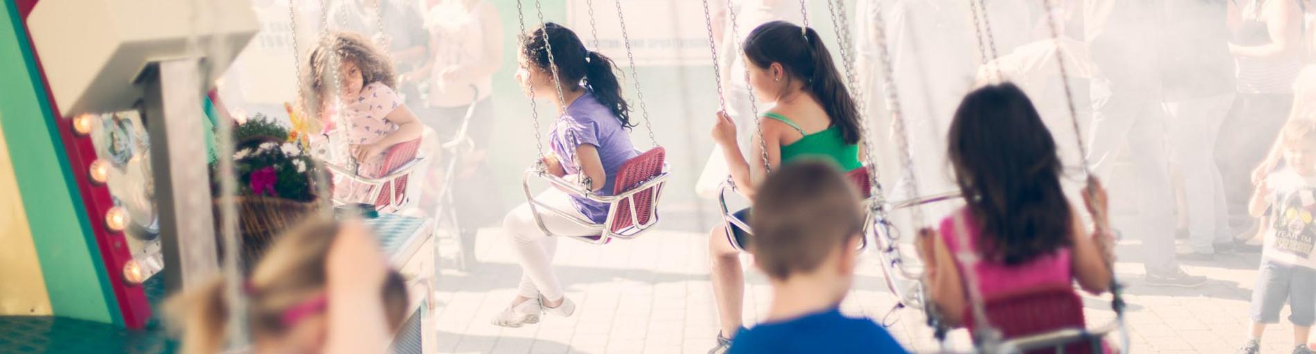 Viele Kinder auf einem Kettenkarussell.