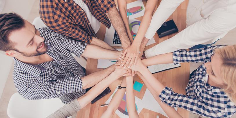 Viele Hände bilden einen Kreis und treffen sich in der Mitte
