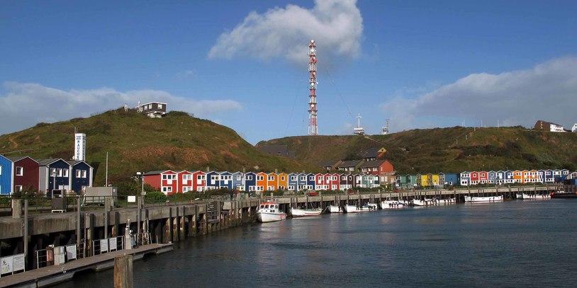 Die Hafenmeile mit vielen bunten Häusern, Berge im Hintergrund und das Meer unten Rechts im Bild. Quelle: Kurverwaltung Helgoland