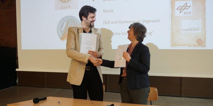 Ein Mann und eine Frau stehen vor einer Präsentationswand, lächeln sich an und geben sich gegenseitig die Hand.