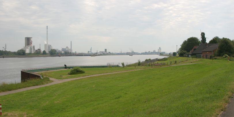 Eine Wiese an einem Fluss, auf der anderen Fluss-Seite sind Industrieanlagen zu sehen; Quelle: Ortsamt Seehausen