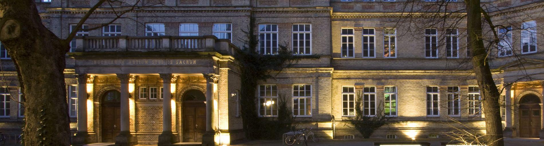 Ein Gebäude mit hellen Steinen in der Dunkelheit.