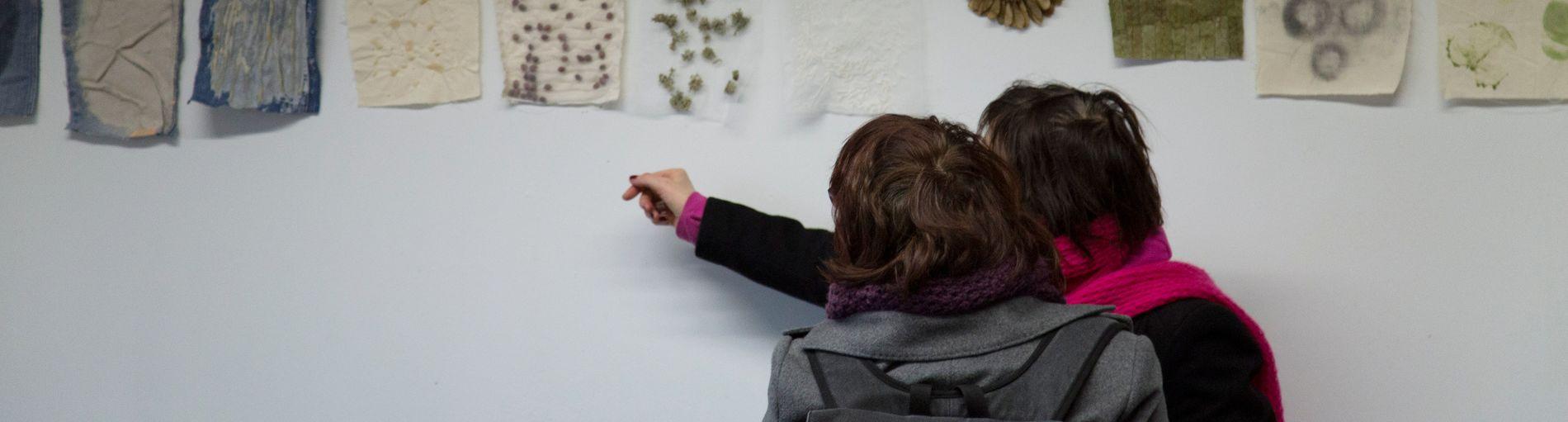 Zwei Frauen schauen sich an einer Wand hängende Exponate an.