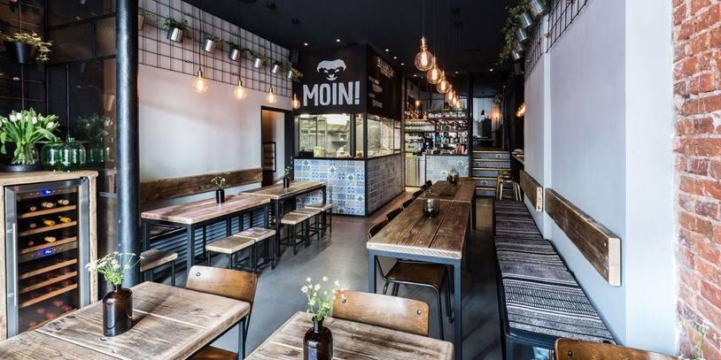 Blick in ein leeres Restaurant mit vielen Holztischen und Stühlen.