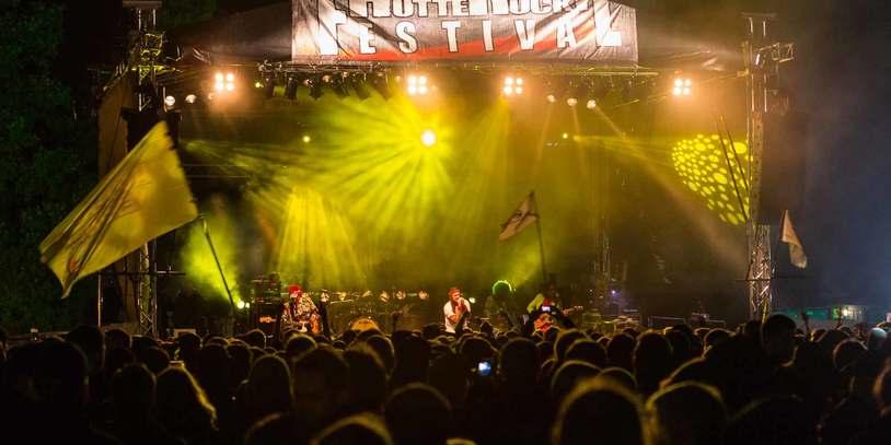 """Eine hellbeleuchtete Bühne auf der eine Band spielt. Im Vordergrund die Köpfe des Publikums. Oberhalb der Bühne hängt der """"Hütte Rockt Festival""""-Banner"""