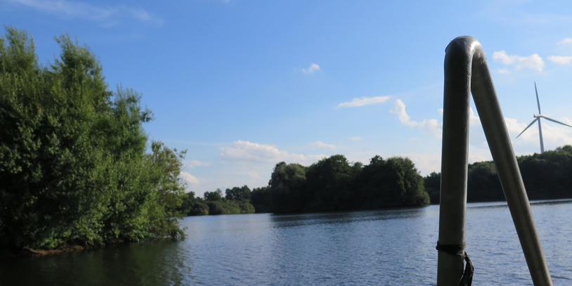 Ein Foto von einem Steg auf das Wasser und eine der Inseln des Mahndorfer Sees.
