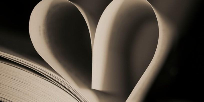 Ein aufgeschlagenes Buch, dessen obersten Seiten zu einem Herz geformt sind.