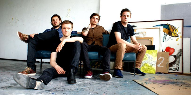 Vier Männer sitzen auf einem Sofa, im Hintergrund stehen Gemälde und Zeichnungen.