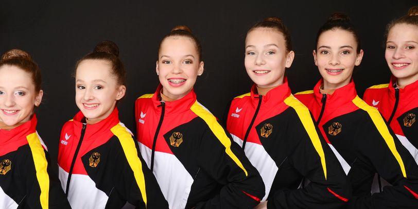 Sechs Sportlerinnen posieren in Trainingsanzügen in schwarz, rot, gold