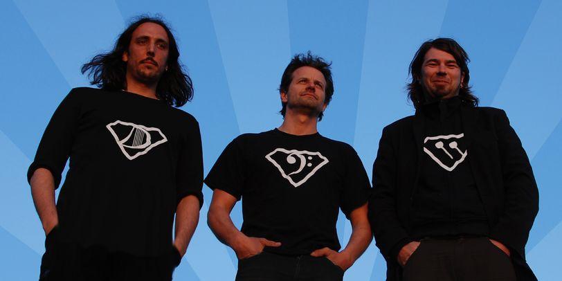 Drei Männer in schwarz gekleidet, stehen vor einem blauen Hintergrund.