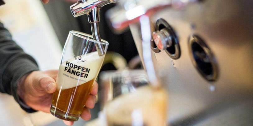 Hände zapfen Bier an einer Zapfanlage
