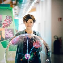 Eine dunkelhaarige Frau berührt eine große Glaskugel mit den Händen